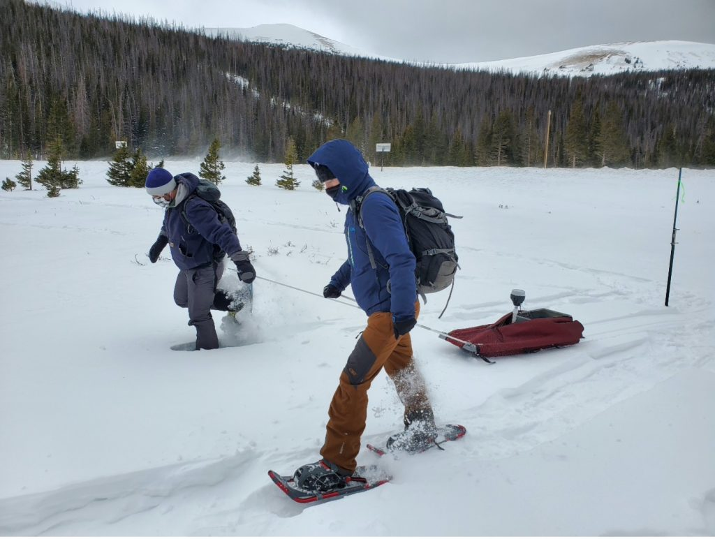 Two scientists trek through the snow to a site in Cameron Pass, Colorado.