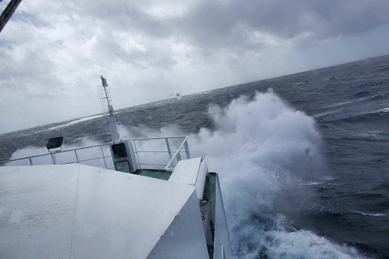 Bow of the R/V Sarmiento de Gamboa crashes through waves during rough seas during one of many stormy days. Credit: Marley Parker