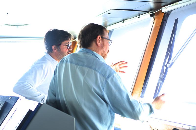 Captain Miguel Ángel Menéndez Pardiñas (left) and co-lead scientist Ken Buesseler (right) discuss operations on the bridge. Credit: Marley Parker