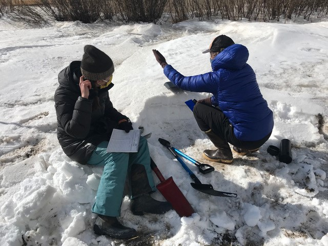 SnowEx researchers Caitlin Mitchell and Marika Feduschak investigate the physical characteristics of the shallow prairie snow. Credit: GEOSWIRL (Geospatial Snow, Water & Ice Resources Lab) / Montana State University