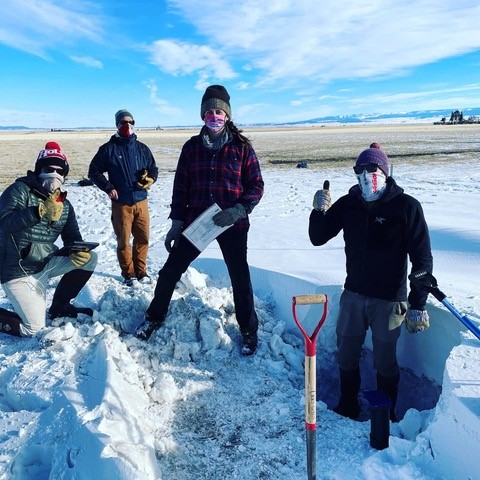 SnowEx researchers Andrew Mullen, Eric Sproles, Caitlin Mitchell, and Ross Palomaki finishing up a snow pit profile. Notice how the snow goes from 3 feet deep to almost nothing over relatively short distances.