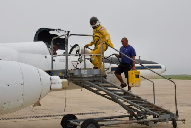 ER-2 Pilot in a pressurized suit steps up a mobile stair to the aircraft.
