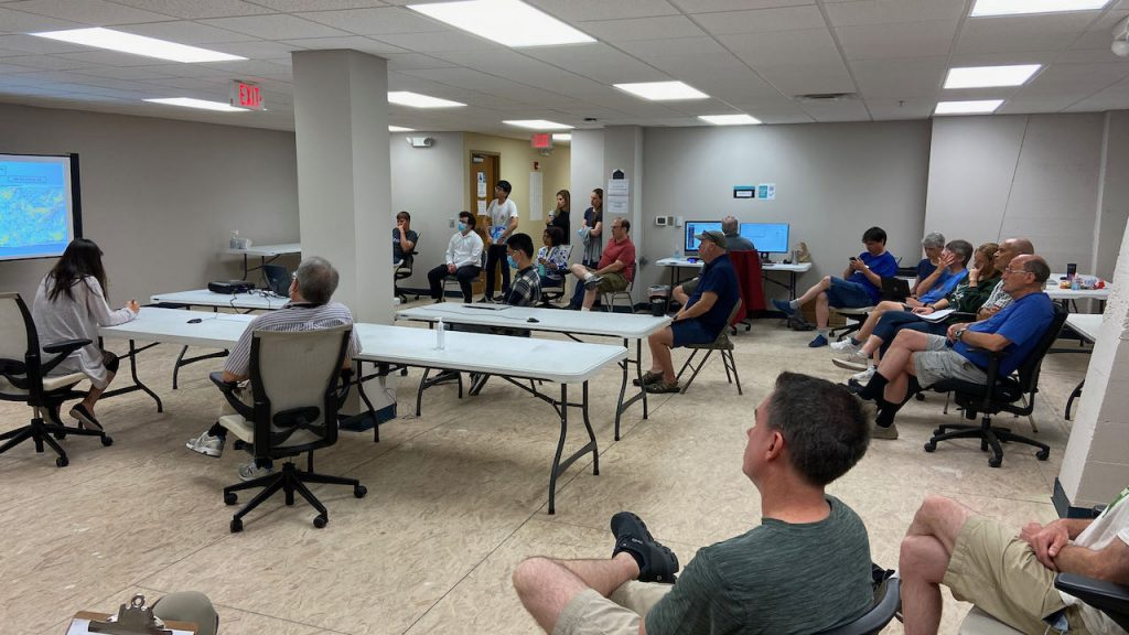 Researchers gathered in a room with tables to plan the flight.