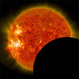 The dark disk of the moon covers the lower-right portion of the sun during a solar eclipse
