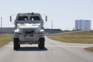 NASCAR Driver Carl Edwards drives MRAP around Pad 39B perimeter and visits the VAB.