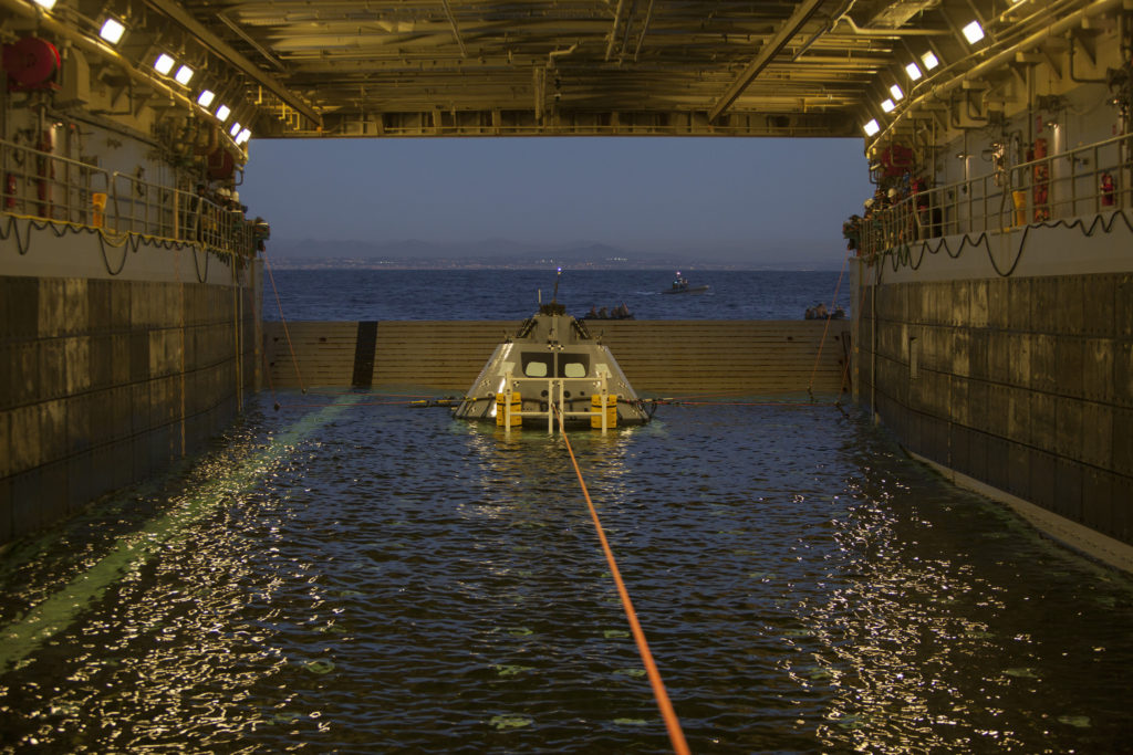 A test version of the Orion capsule is pulled into the well deck of the USS Anchorage during Underway Recovery Test 6.