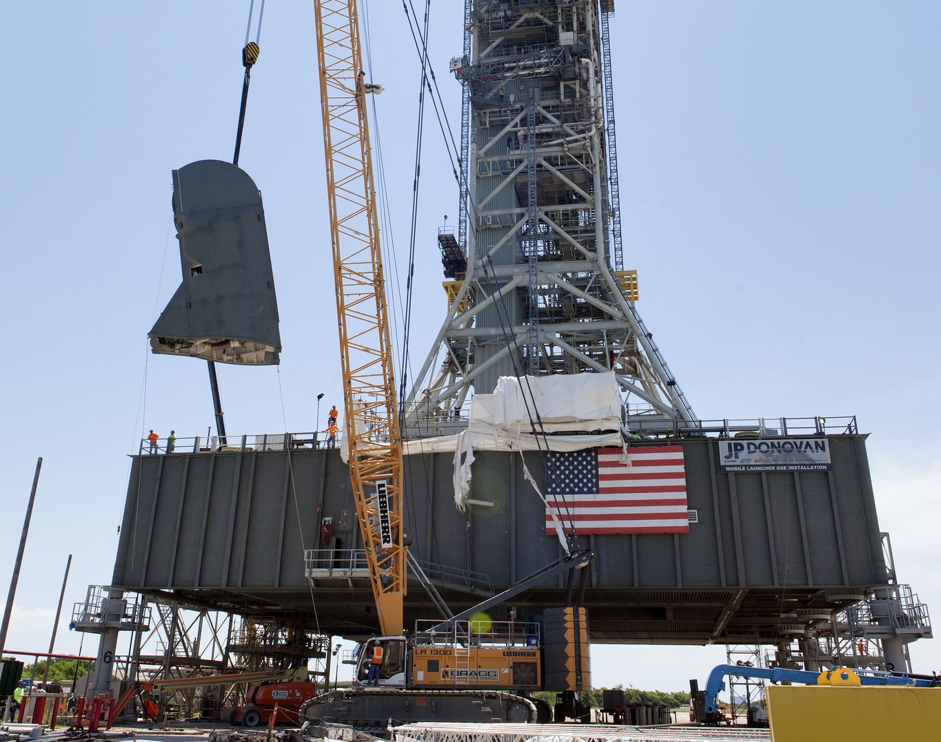 The first of two Tail Service Mast Umbilicals is lifted for installation on the mobile launcher July 12, 2018, at NASA's Kennedy Space Center in Florida.