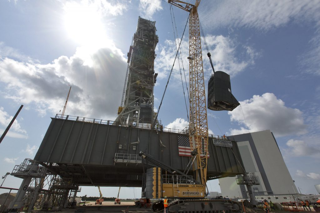 A crane lifts the second of two tail service mast umbilicals up for installation on the 0-level deck of the mobile launcher on July 27, 2018, at NASA's Kennedy Space Center in Florida.