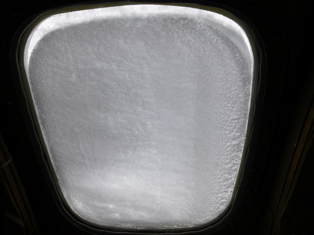 Windblown snow covers one of the P-3's side windows