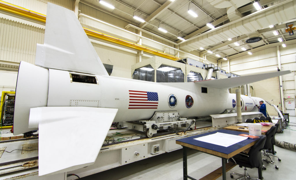 In Building 1555 at Vandenberg Air Force Base in California, preflight processing nears completion for a Northrup Grumman Pegasus XL rocket on Oct. 8, 2018. Enclosed in the rocket's payload fairing is NASA's Ionospheric Connection Explorer, or ICON, satellite.  Photo credit: NASA/Randy Beaudoin