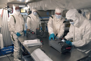 Technicians and engineers prepare a P-POD container for installation on the Delta II rocket launching JPSS-1.