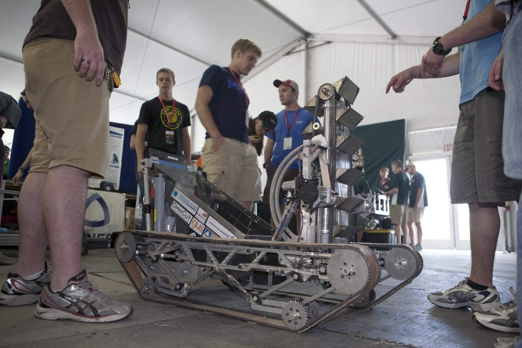 Inside the robot pit preparation facility at NASA's Kennedy Space Center Visitor Complex in Florida, college team members look over their custom-made robot in preparation for NASA's Robotic Mining Competition.
