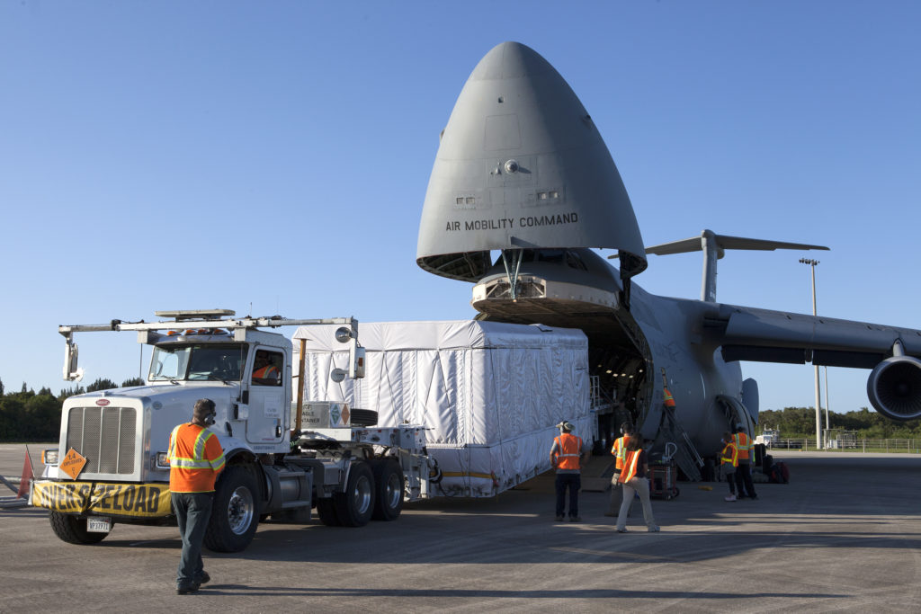 A truck with a specialized transporter drives out of the cargo hold of an Air Force C-5 Galaxy transport plane at the Shuttle Landing Facility at NASA's Kennedy Space Center in Florida to deliver the GOES-R spacecraft for launch processing.