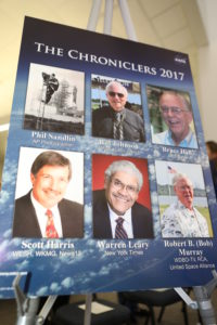 "A poster in the NASA News Center at Kennedy Space Center in Florida bears the names and photos of the six new honorees added to the facility's ""Chroniclers"" roll of honor."