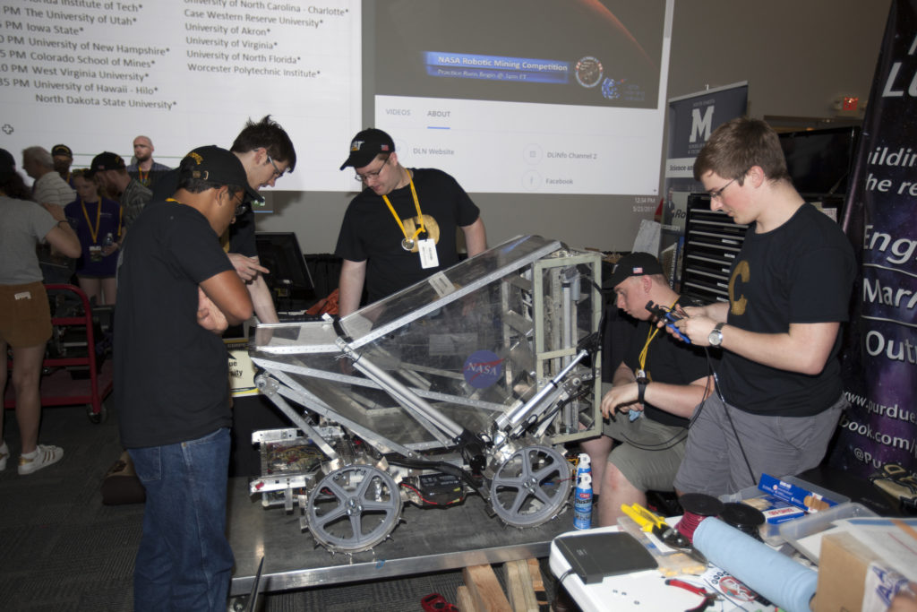 Team members from Purdue University prepare their robot miner in the RoboPit at NASA's 8th Annual Robotic Mining Competition at the Kennedy Space Center Visitor Complex in Florida.