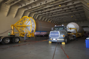 At Port Canaveral in Florida, a United Launch Alliance Atlas V first stage booster and Centaur upper stage are about to be transported from the company's Mariner ship to Cape Canaveral Air Force Station.