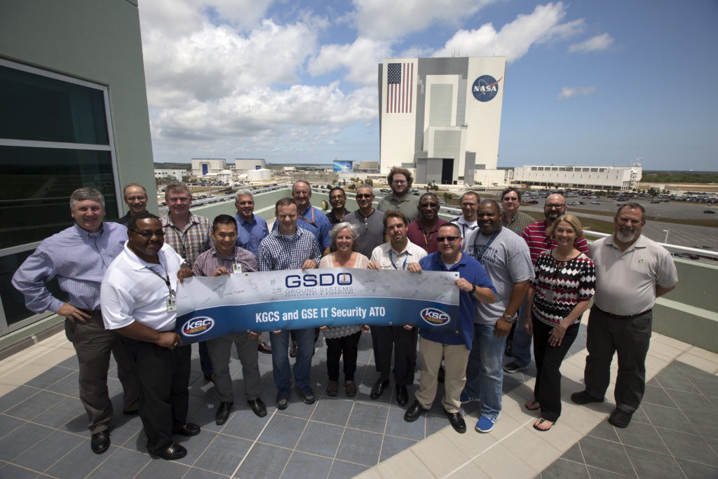 The Kennedy Ground Control System team poses after signing a banner at Kennedy Space Center's Operations Support Building II.