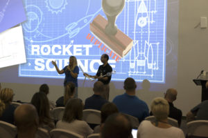 Education Specialists Lynn Dotson, left, of the NASA Public Engagement Center, and Lester Morales, right, of Texas State University's NASA STEM Educator Professional Development Collaborative, explain the Rocketry Engineering Design Challenge to teachers participating in the 2017 GE Foundation High School STEM Integration Conference at the Center for Space Education at NASA's Kennedy Space Center.