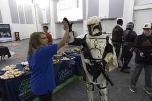 A middle-school student high-fives a Star Wars character from the 501st Legion in the Center for Space Education at NASA's Kennedy Space Center in Florida.