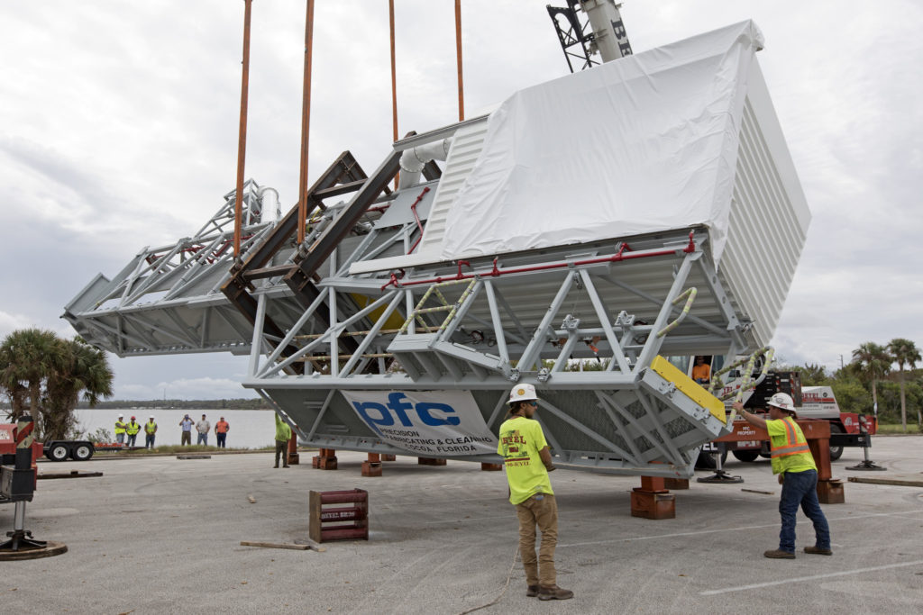 Two heavy-lift cranes are used to tilt and lower the Orion crew access arm onto a work stand in a storage location Oct. 17, 2017, at NASA's Kennedy Space Center in Florida.