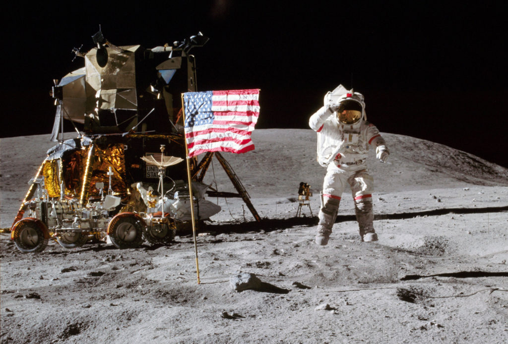 Apollo 16 commander John Young leaps from the lunar surface as he salutes the United States flag at the Descartes landing site during the mission's first moon walk. The Lunar Module is on the left and the Lunar Roving Vehicle is parked in front. Photo credit: NASA/Charlie Duke