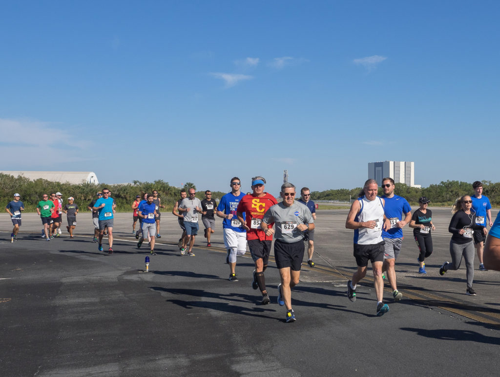 Kennedy Space Center Director Bob Cabana, center, is joined by a large group of center employees and guests as they participate in the KSC Walk Run on the Shuttle Landing Facility runway.