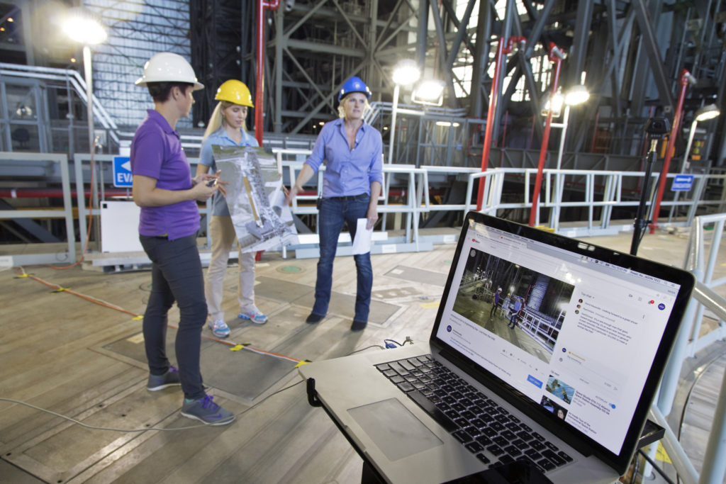 The laptop computer in the foreground displays Rachel Power, left, of NASA's Digital Expansion to Engage the Public (DEEP) Network; Bethanne' Hull, center, of NASA Outreach; and NASA engineer Krista Shaffer inside Kennedy Space Center's Vehicle Assembly Building during Introduce a Girl to Engineering Day.