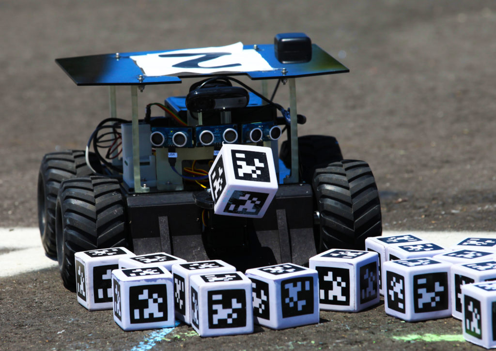 "At the 2017 competition, a Swarmie robot finds a ""resource"" cube marked with an AprilTag. In the Swarmathon competition, students were asked to develop computer code for the small robots, programming them to look for ""resources"" in the form of cubes with AprilTags. Photo credit: NASA/Kim Shiflett"
