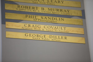 Brass strips engraved with the names of Craig Covault and George Diller were unveiled during a ceremony at Kennedy Space Center's NASA News Center in Florida on Friday, May 4.
