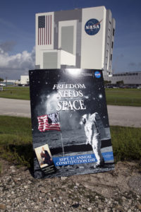 "Kennedy Space Center's ""Freedom Needs Space"" poster is near the Vehicle Assembly Building"