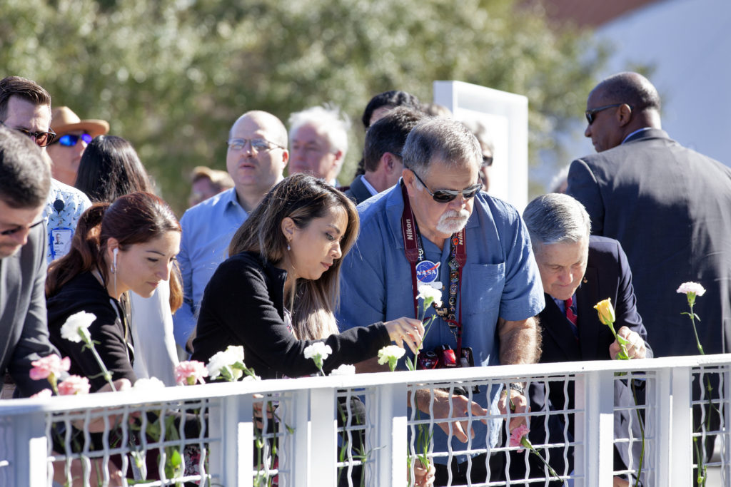 Kennedy Space Center Director Bob Cabana and guests place flowers in front of the Space Mirror Memorial at the Kennedy Space Center Visitor Complex during this year's Day of Remembrance ceremony.