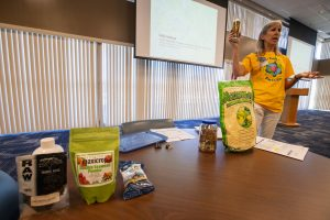 Sally Scalera, urban horticulture agent and master gardener coordinator from the University of Florida's Institute of Food and Agricultural Sciences Brevard Extension Office, shows Kennedy Space Center employees some sustainable yard products available during her presentation on tips and tricks for a healthy yard and garden on April 24, 2019. Photo credit: NASA/Cory Huston