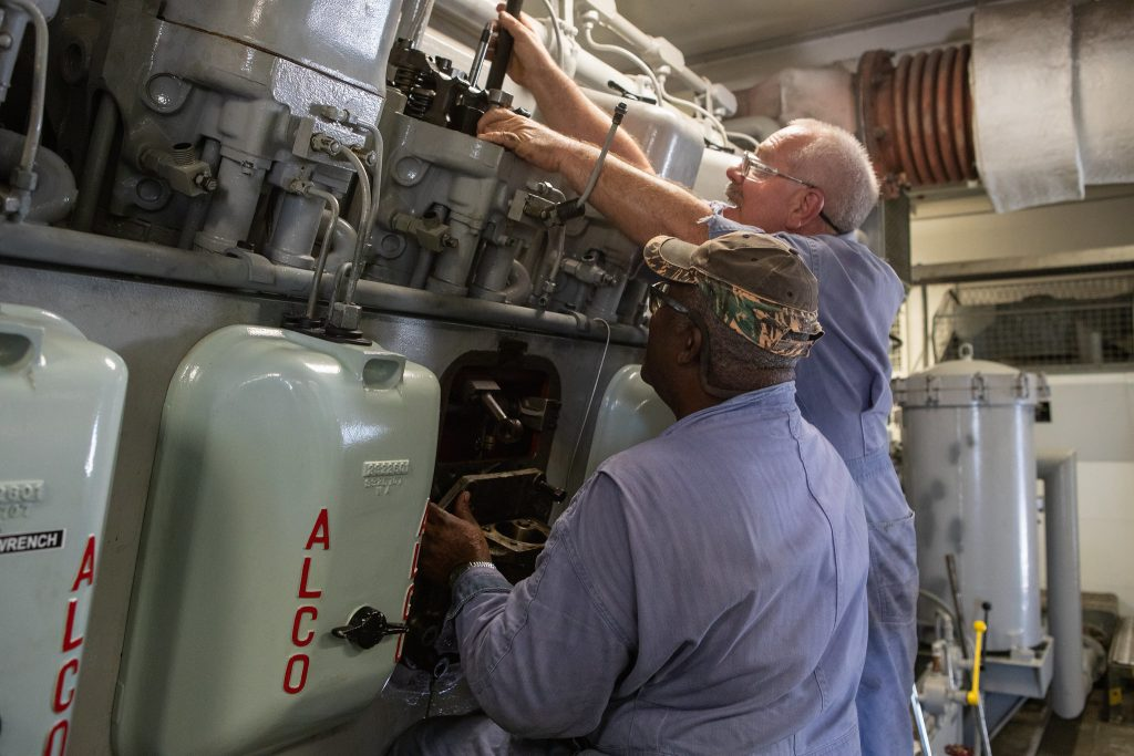 Pat Brown, left, and William Vardaman, mechanical technicians with the Jacobs contracting team, perform engine maintenance on NASA's crawler-transporter 2 on March 26, 2019.