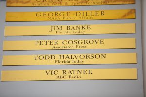Brass strips engraved with the names of Jim Banke, Peter Cosgrove, Todd Halvorson and Vic Ratner were unveiled during a ceremony on May 3, 2019, at Kennedy Space Center's NASA News Center in Florida. Banke, Halvorson, Ratner and Cosgrove were honored as members of The Chroniclers, which recognizes retirees of the news and communications business who have helped spread news of American space exploration from Kennedy for 10 years or more.