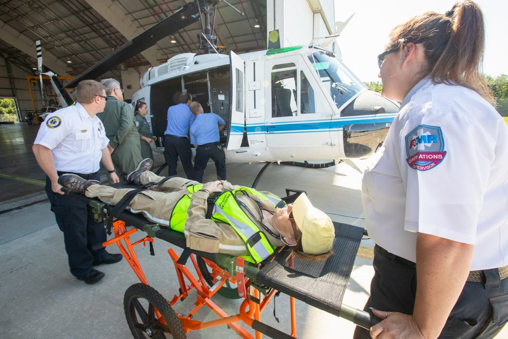 "Kennedy Space Center personnel and American Medical Response (AMR) contractor paramedics prepare to load a ""patient,"" a KEMCON Fitness Center staff member, into a NASA helicopter during a medical support training course in the Space Florida hangar at the spaceport's Shuttle Landing Facility on May 17, 2019."