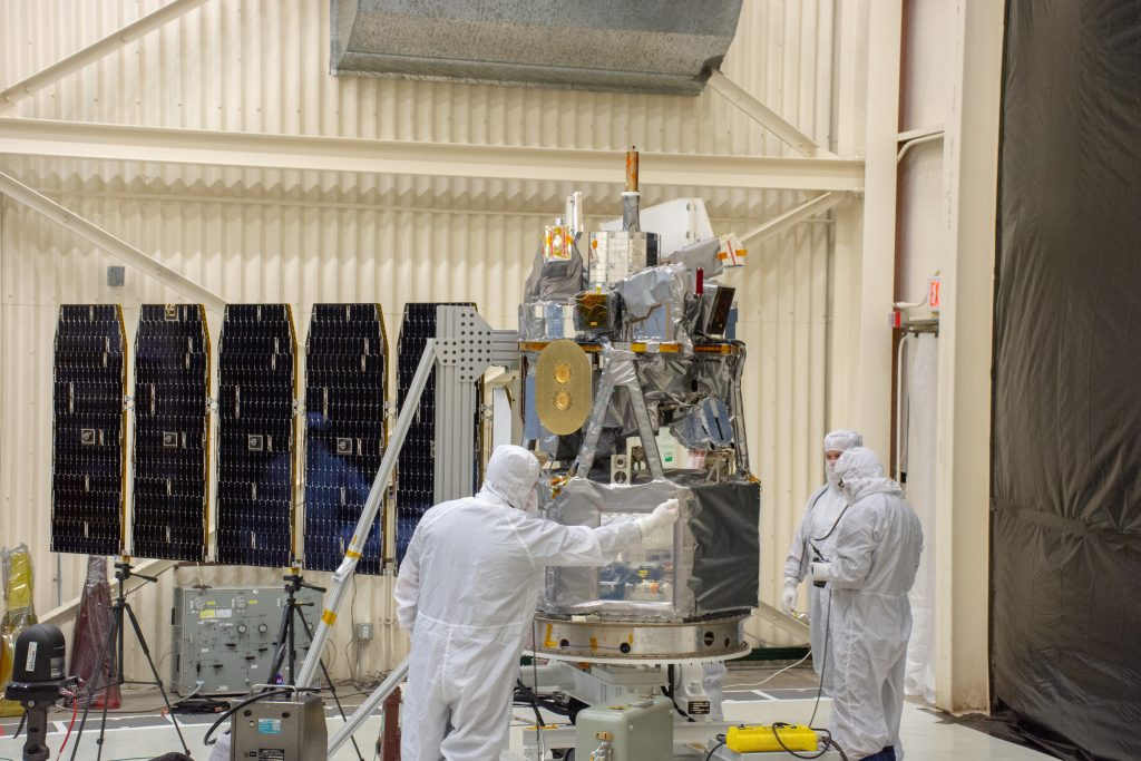 Technicians extend the solar array on NASA's Ionospheric Connection Explorer (ICON) during a deployment test inside Building 1555 at Vandenberg Air Force Base in California on Aug. 10, 2019.