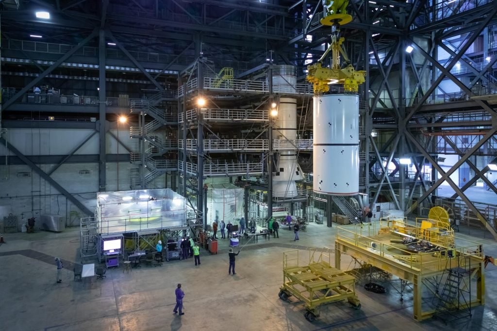 In High Bay 4 of the Vehicle Assembly Building at NASA's Kennedy Space Center in Florida, a crane moves Space Launch System (SLS) solid rocket booster pathfinder segments to stack them atop other pathfinder segments during a training exercise on Jan. 8, 2020.
