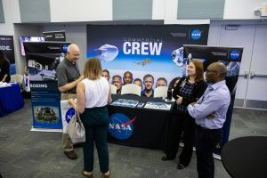 Steve Payne, far left, with NASA's Commercial Crew Program, visits with a guest during a Community Leaders Update hosted by Kennedy Space Center on Feb. 18, 2020.
