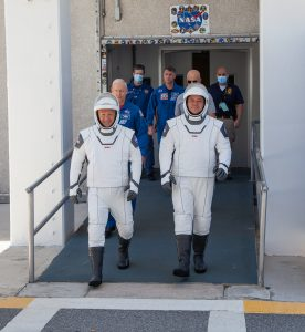 On May 23, 2020, Demo-2 crew members Robert Behnken (right) and Douglas Hurley walk out of the Neil A. Armstrong Operations and Checkout Building as they prepare to be transported to historic Launch Complex 39A during a dress rehearsal ahead of NASA's SpaceX Demo-2 launch.
