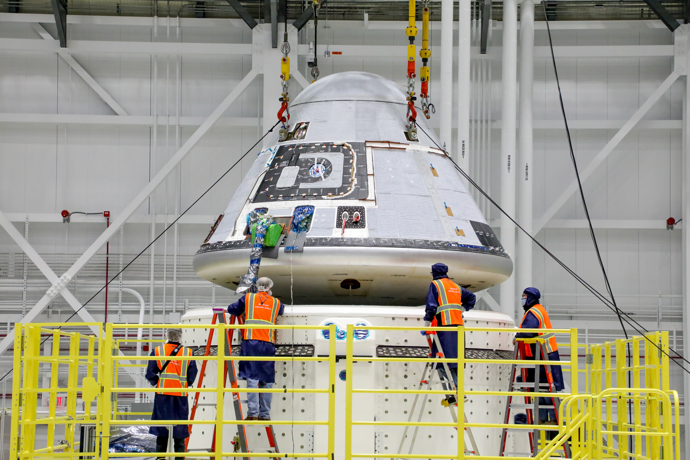 Technicians observe Boeing's Starliner crew module being placed on top of the service module in the Commercial Crew and Cargo Processing Facility at NASA's Kennedy Space Center in Florida on Jan. 14, 2021.