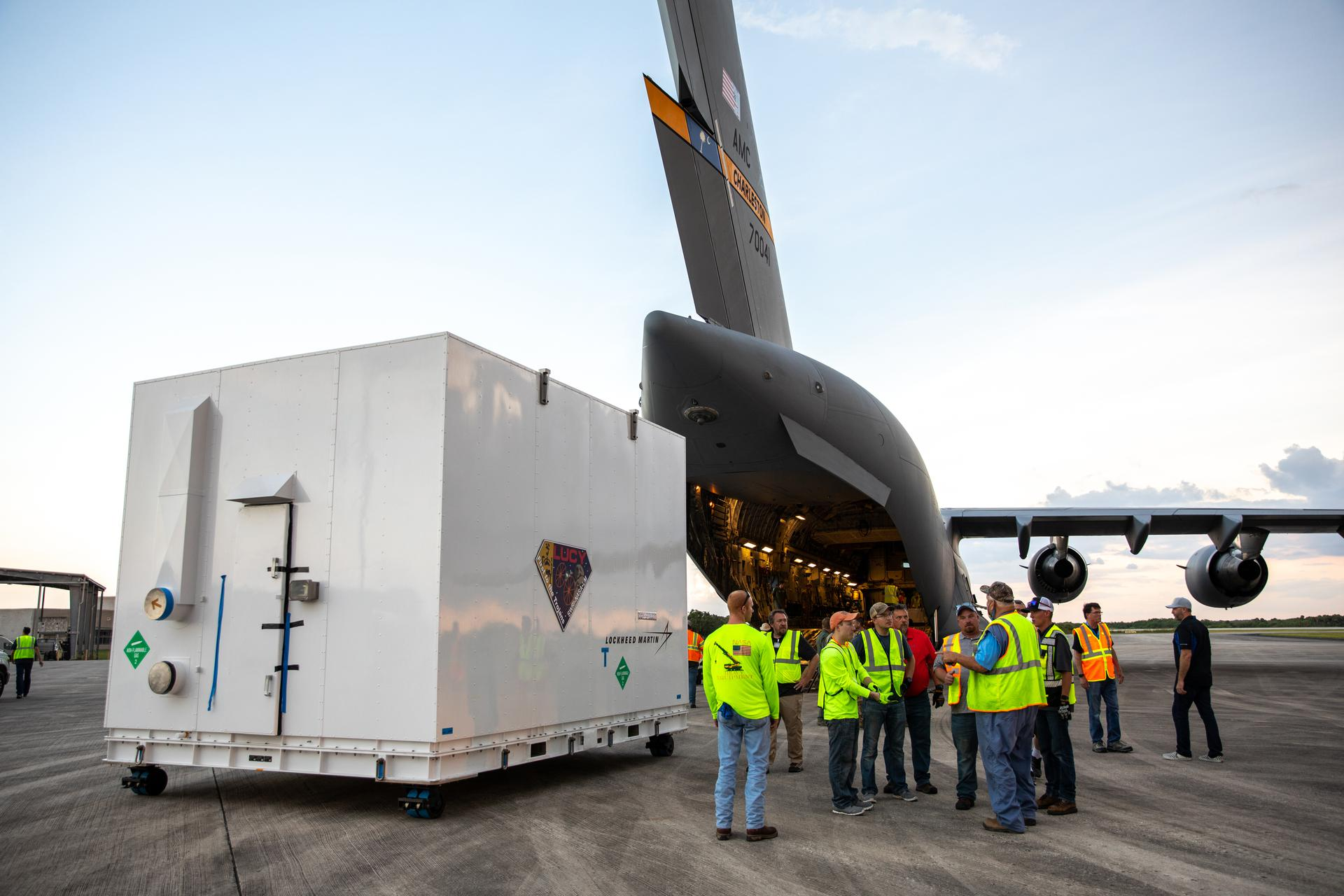 The shipping container holding NASA's Lucy spacecraft is unloaded from an Air Force C-17 cargo plane on the runway of the Launch and Landing Facility at Kennedy Space Center in Florida on July 30, 2021.