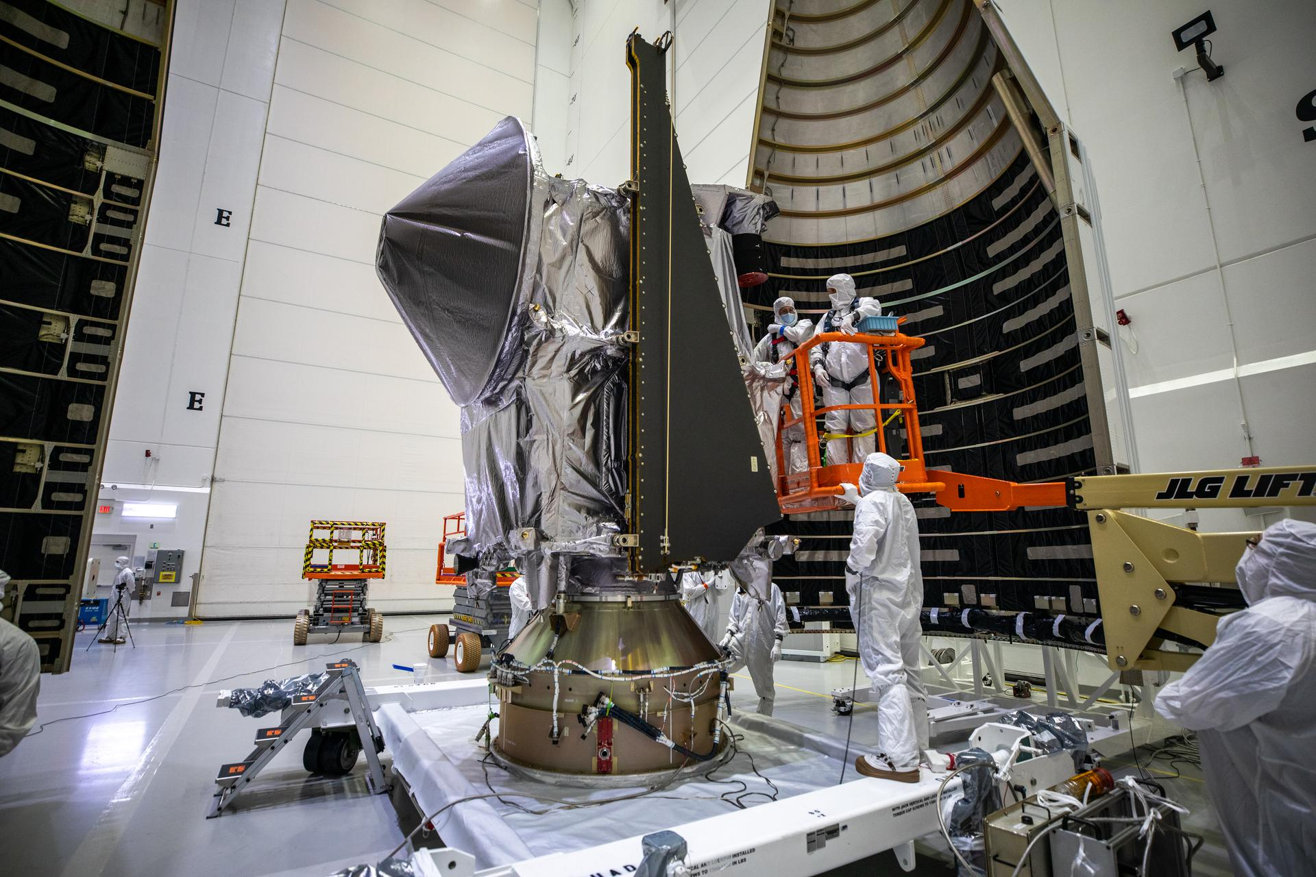 Workers inside the Astrotech Space Operations Facility in Titusville, Florida, move the first half of the United Launch Alliance (ULA) payload fairing toward NASA's Lucy spacecraft on Sept. 30, 2021.