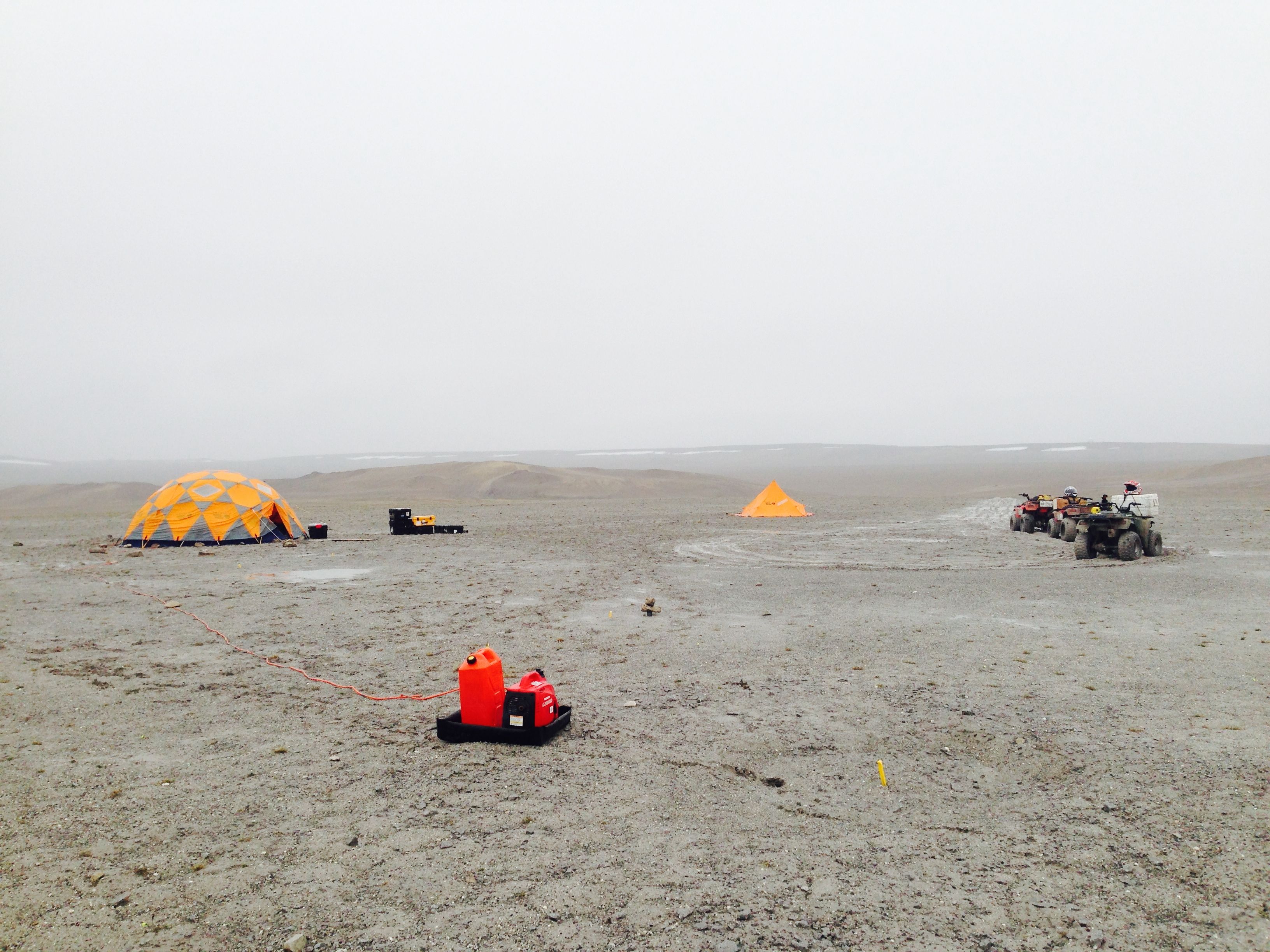"""Drill and robotic test camp inside Haughton Crater. """"Drill Hill""""'s impact breccia and permafrost make it an excellent textural analog for Mars drilling tests."""
