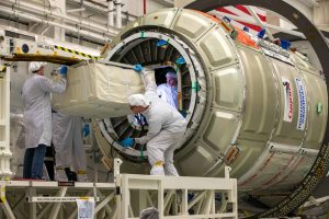 technicians in clean suits loading rectangle cloth container into cylinder spacecraft.