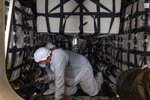 technicians in clean suits inside of spacecraft