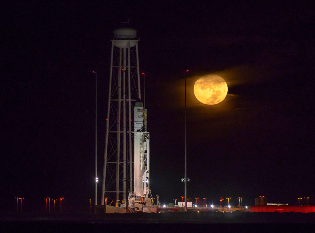 rocket on the pad with orange moon behind