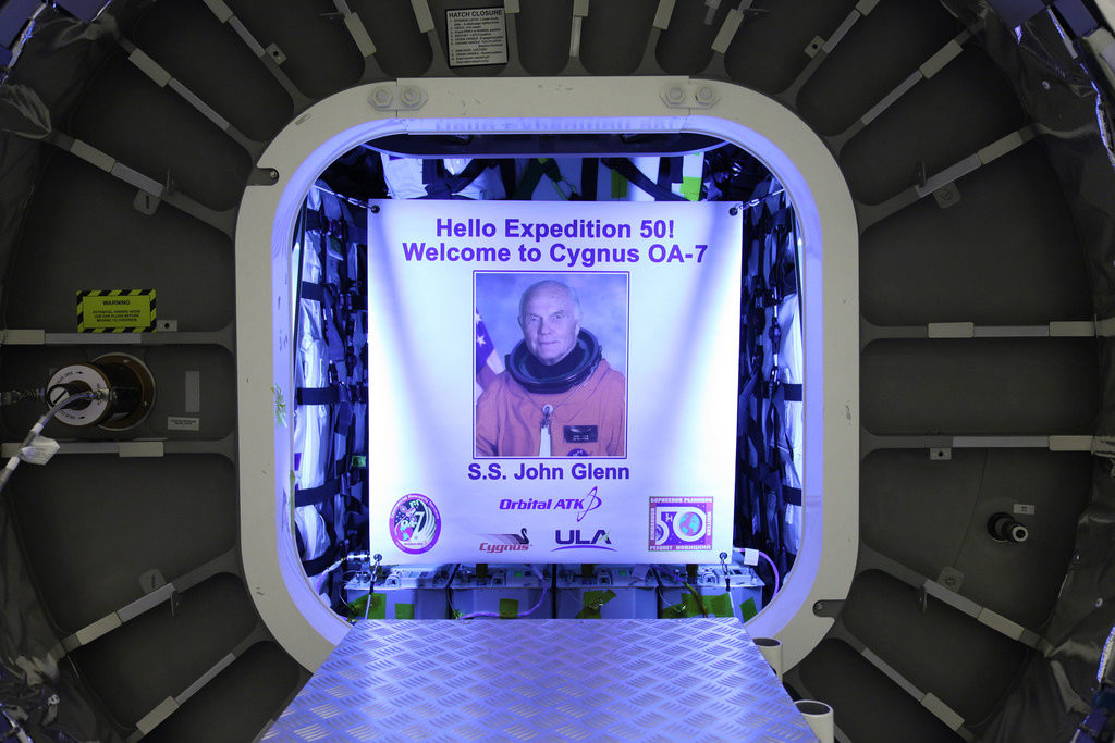 Inside the Payload Hazardous Servicing Facility at NASA's Kennedy Space Center in Florida, the John Glenn banner is attached inside the Orbital ATK Cygnus pressurized cargo module. The Cygnus cargo module has been renamed the S.S. John Glenn to honor the late former Project Mercury and space shuttle astronaut.