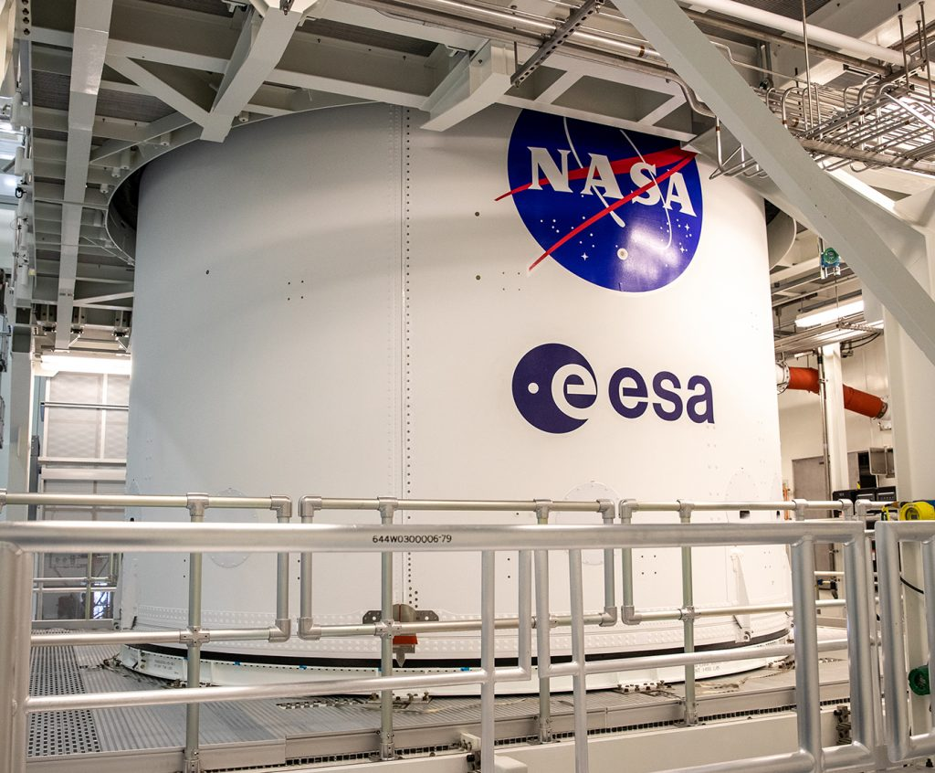 The NASA and ESA logos are visible on the Orion spacecraft adapter jettison fairing in the MPPF at Kennedy Space Center.