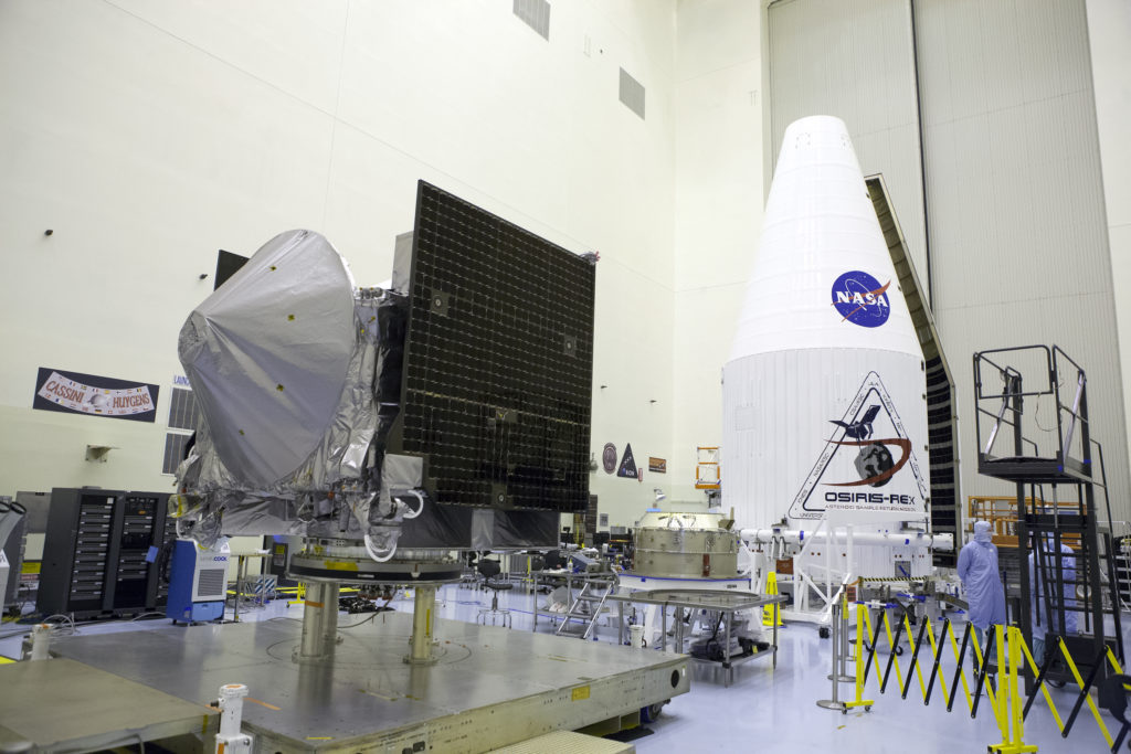 The OSIRIS-REx spacecraft, foreground, is prepared for encapsulation in its payload fairing, visible in the background