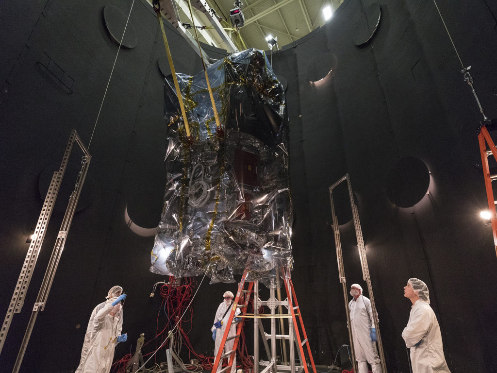 The spacecraft is lowered into the thermal vacuum chamber